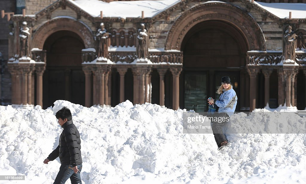 A woman sits on a mound of snow in Copley Square following a powerful blizzard on February 10, 2013 in Boston, Massachusetts. The storm dumped more than two feet of snow in parts of New England and more than 200,000 Massachusetts customers remain without power.