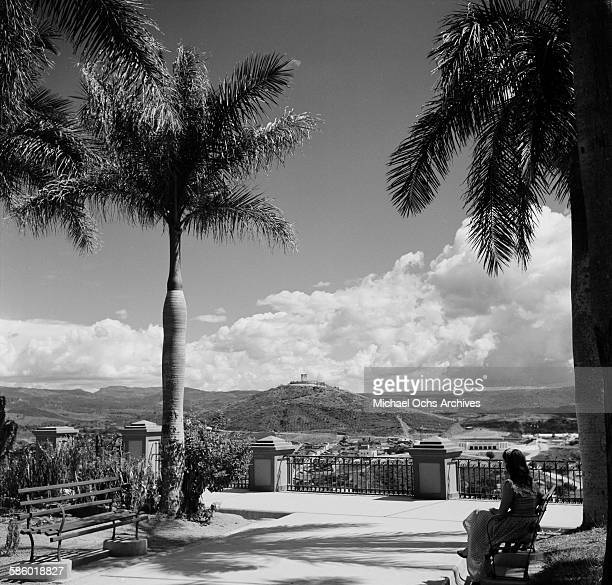 A woman sits on a park bench looking at Monumento a la Paz in Tegucigalpa Honduras