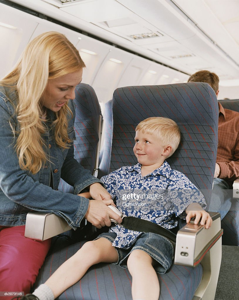Woman Sits on a Plane With Her Young Son, Adjusting His Seat Belt : Stock Photo
