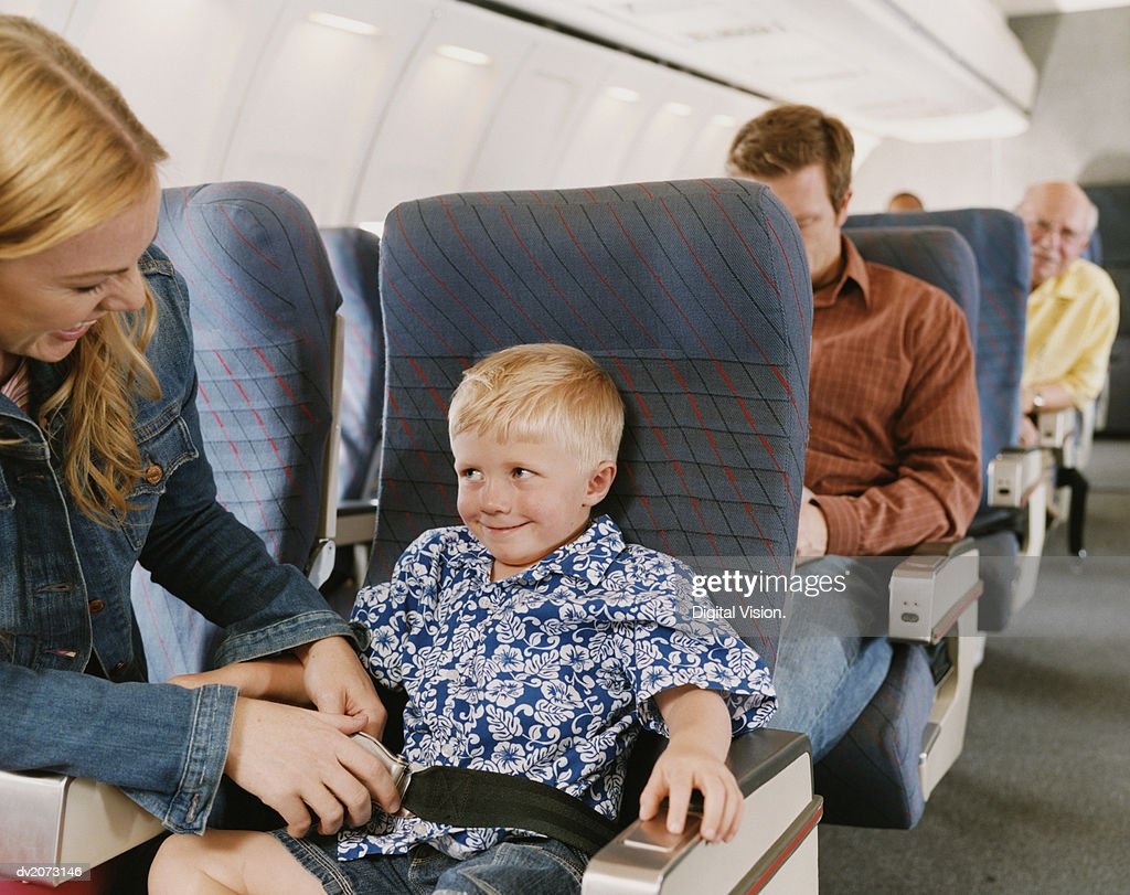 Woman Sits on a Plane With Her Young Son, Fastening His Seat Belt : Stock Photo