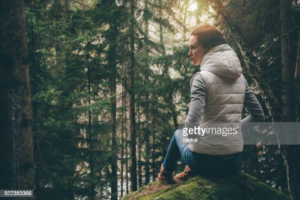Woman sits on a rock in forest and looking around