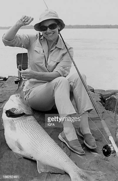 A woman sits on a rocky shoreline holding a golden dorado caught while on a Tiger Hill Safari near Paraguay circa 1970