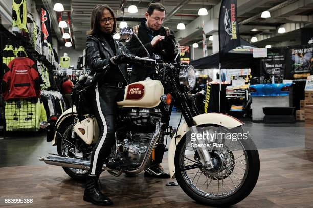 A woman sits on a Royal Enfield motorcycle on the floor at the Progressive International Motorcycle Show at the Javits Center on December 1 2017 in...
