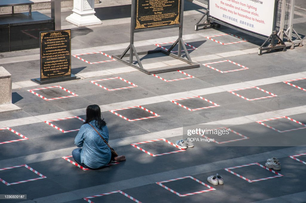 A woman sits on a social distancing square while praying in... : ニュース写真