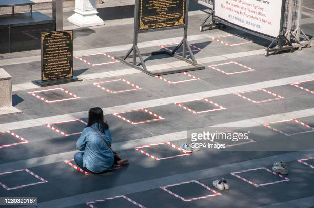 Woman sits on a social distancing square while praying in front of a shrine near Ratchadamri Road. The Thai government has applied social distancing...