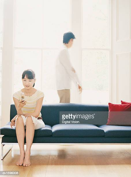 Woman Sits on a Sofa Using a Mobile Phone, Man Walks by Windows
