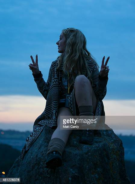 A woman sits on a stone at the Stone Circle at Worthy Farm in Pilton on the first day of the 2014 Glastonbury Festival on June 25 2014 in Glastonbury...