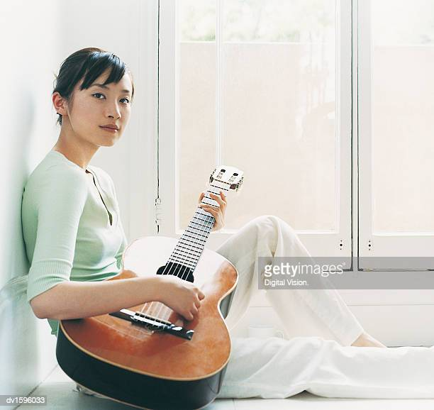 Woman Sits on a Tiled Floor Playing the Guitar