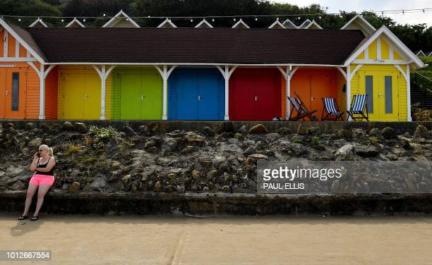 A woman sits on a wall enjoying the sunshine outside coloured beach huts at North Bay Scarborough northern England on August 7 2018 as Europe...