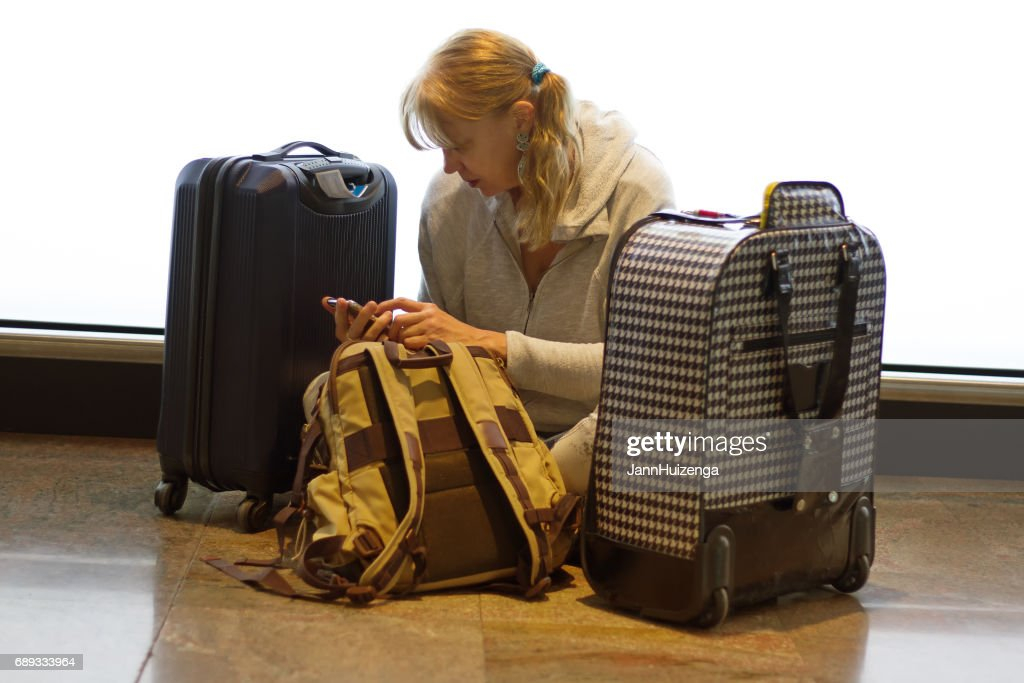 Woman Sits on Aiport Floor Reading Phone, Surrounded by Luggage : Stock Photo