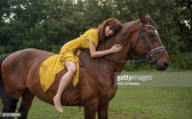 Woman sits on brown horse and hugs it
