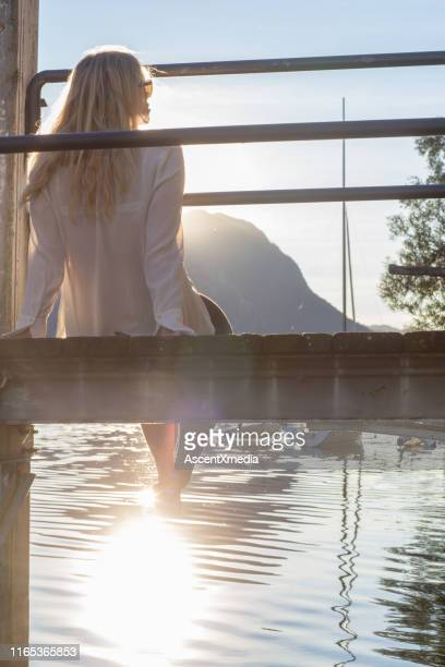 woman sits on dock over lake in the sunlight - early retirement stock pictures, royalty-free photos & images