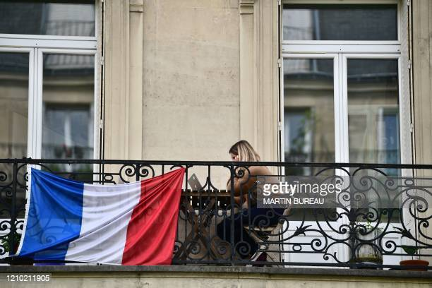 A woman sits on her balcony looking at her laptop in Paris on April 17 on the 32nd day of a lockdown across France aimed at curbing the spread of the...
