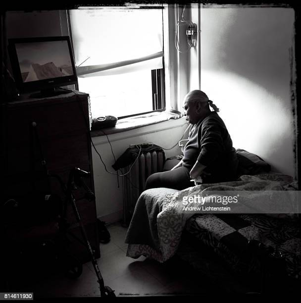 A woman sits on her bed in her single room occupancy home in the YWA on May 31 2017 in downtown Brooklyn New York Located in the heart of rapidly...