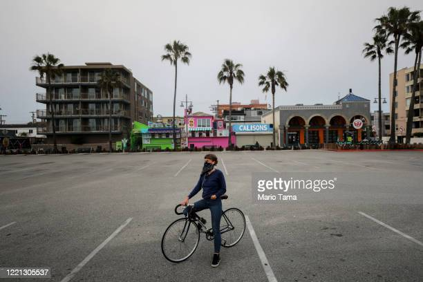 A woman sits on her bike in a shuttered Venice Beach parking lot which remains closed along with all other Los Angeles County beaches under...