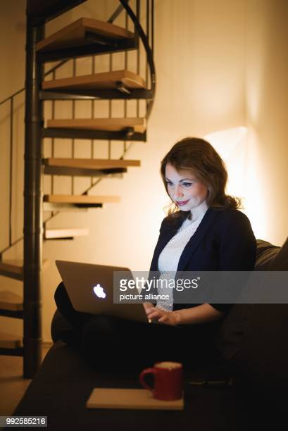 ILLUSTRATION A woman sits on her couch inside her home working on a laptop in Rattelsdorf Germany 24 October 2017 With the spread of digitalization...