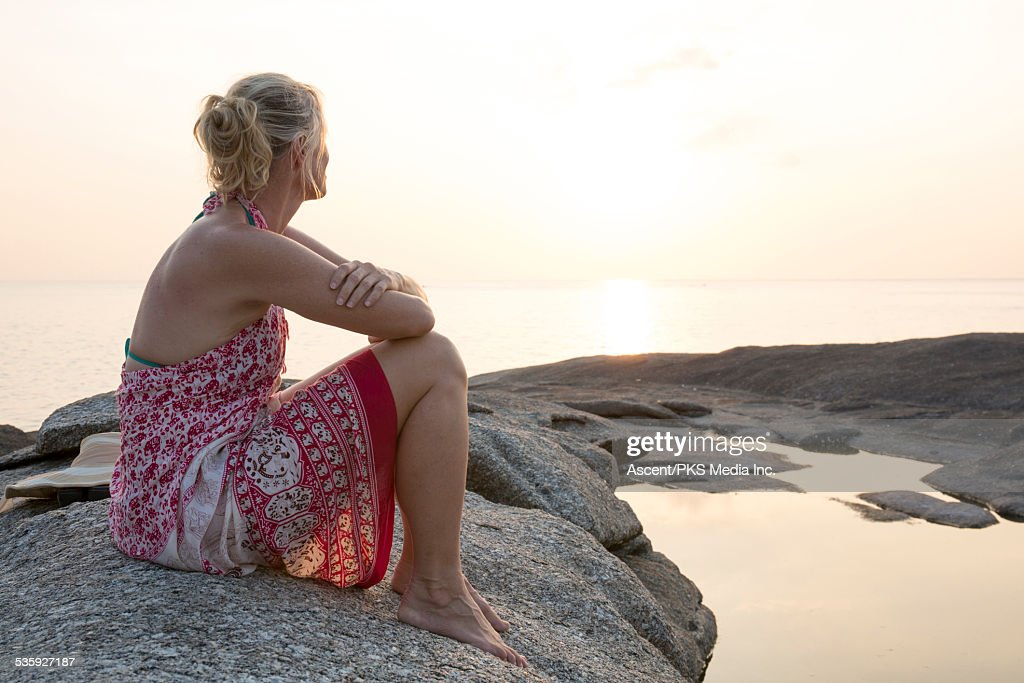 Woman sits on rocks above pool, looks to sea, sun : Stock Photo