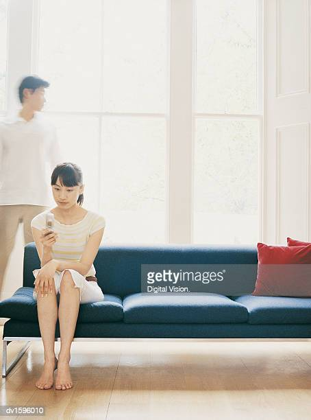 Woman Sits on Sofa With Mobile Phone, Man Stands Behind by Windows
