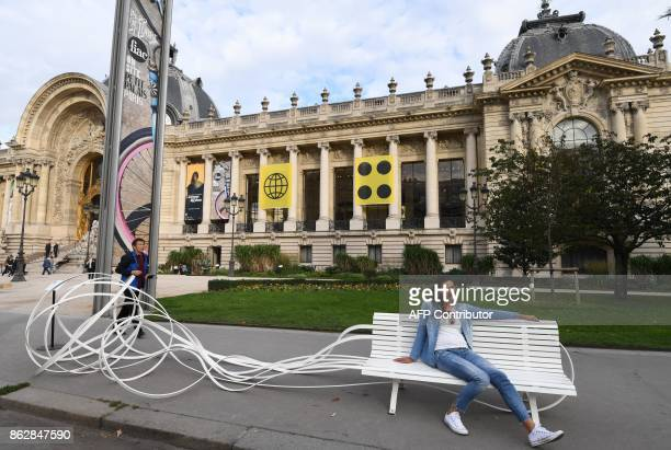 A woman sits on the artwork by Pablo Reinoso 'Simple Talk 2017' as she visits the Paris International Contemporary Art Fair at the Grand Palais in...