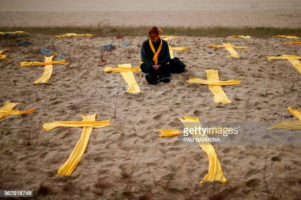 TOPSHOT A woman sits on the beach among yellow clothes shaped as crosses during a protest in support for jailed separatist leaders called by local...