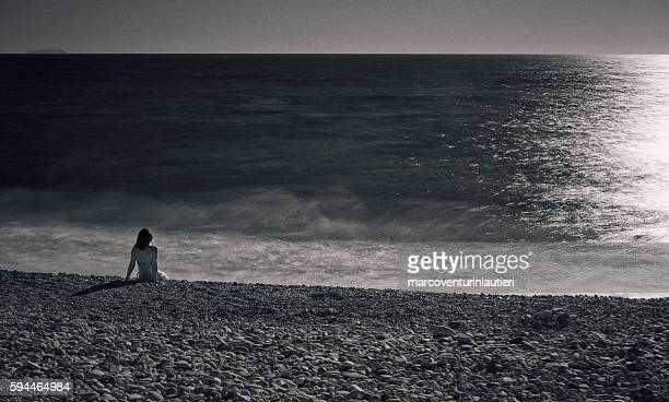 Woman sits on the beach at the sunset