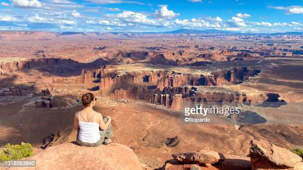 a woman sits on the edge of a canyon in canyonlands national park - fitopardo stock pictures, royalty-free photos & images
