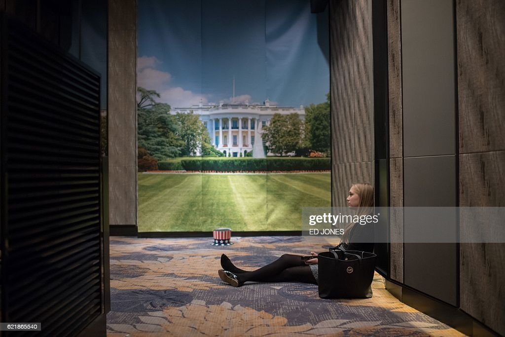 TOPSHOT - A woman sits on the floor at an election event organised by the US embassy, at a hotel in Seoul on November 9, 2016. Donald Trump's stunning performance in the US presidential election triggered shock and angst in Asia, where observers fretted over the implications for everything from trade to human rights and climate change. / AFP / Ed JONES
