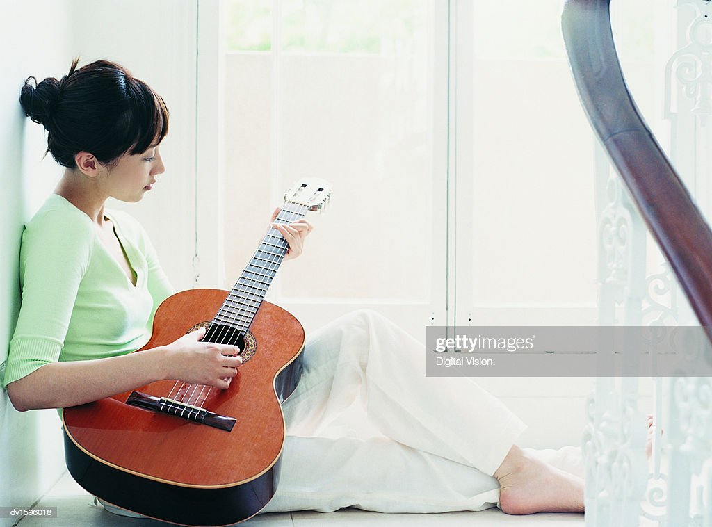 Woman Sits on the Floor Playing the Guitar, Domestic Interior : Stock Photo