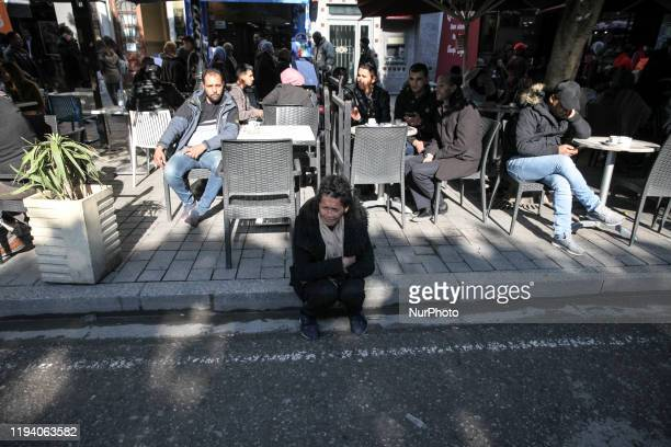 A woman sits on the ground in front of men sitting in at cafe as Tunisians attend the celebrations of the 9th anniversary of the revolution on avenue...