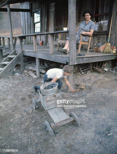 A woman sits on the porch of a log house as a child is playing in front of it with a bucket of coal Pike County Kentucky US 1967