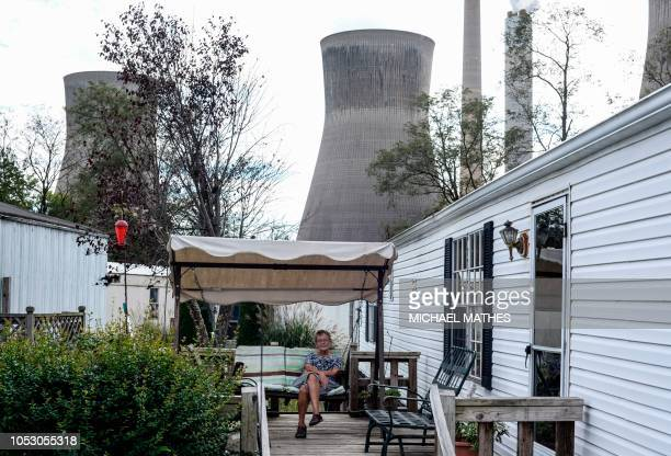Woman sits on the porch of her home against the backdrop of a power plant in Winfield, West Virginia, October 19, 2018. US Senator Joe Manchin is one...
