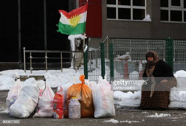 A woman sits on the snow with Kurdish flags in the background at the IranIraq border crossing of Haji Omran on January 3 one day after two border...