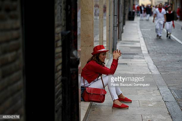 A woman sits on the street during the sixth day of the San Fermin Running of the Bulls festival on July 11 2014 in Pamplona Spain The annual Fiesta...
