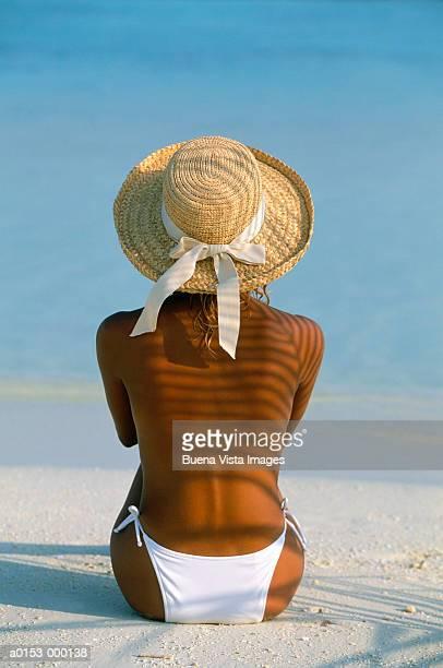 woman sits on tropical beach - espalda chica morena playa fotografías e imágenes de stock