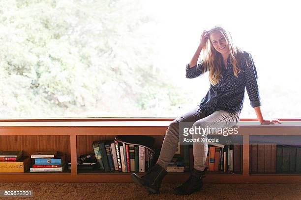 Woman sits on window ledge of home, above books