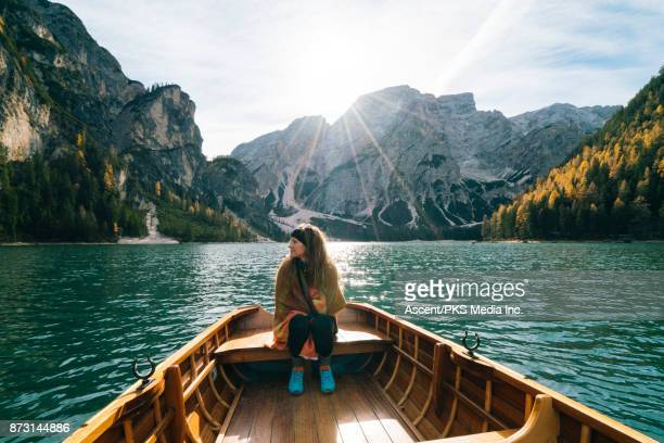 Woman sits on wooden rowboat on alpine lake