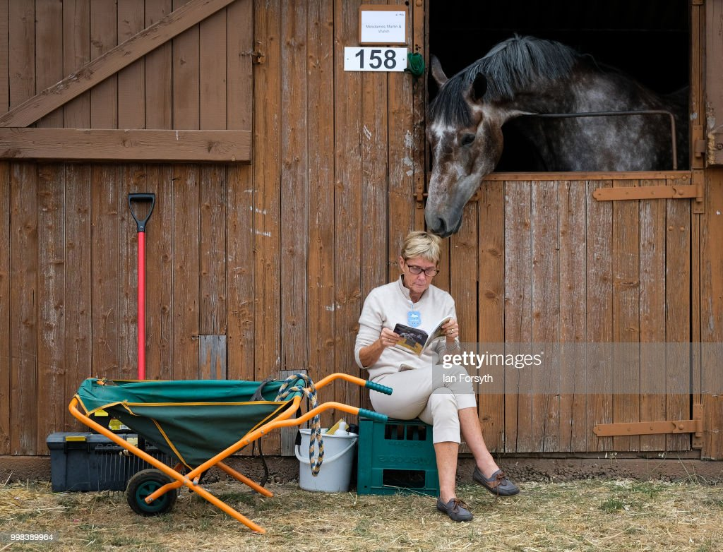 A woman sits outside a stable as a horse sniffs her head during the final day of the 160th Great Yorkshire Show on July 12, 2018 in Harrogate, England. First held in 1838 the show brings together agricultural displays, livestock events, farming demonstrations, food, dairy and produce stands as well as equestrian events. The popular agricultural show is held over three days and celebrates the farming and agricultural community and their way of life.