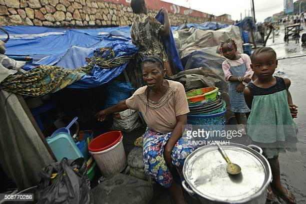 Woman sits outside her flooded makeshift home in Kinshasa on February 5, 2016. For the last seven months 167 DR Congo families have lived in the...