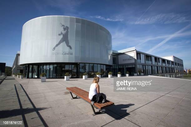 "Woman sits outside the ""Rafa Nadal Academy"" in Manacor on the Spanish Balearic island of Majorca, on October 11, 2018."