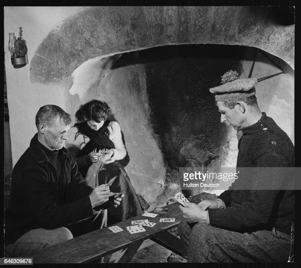 A woman sits sewing as two men play a game of cards at home in the Aran Islands Republic of Ireland 1953