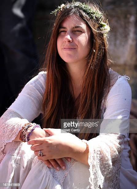 A woman sits to watch a Beltane May Day celebration in Glastonbury main street on May 1 2013 in Glastonbury England Although more synonymous with...