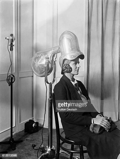 Woman sits under a new salon hair dryer with a tall silver helmet at a London trade fair, 1928.