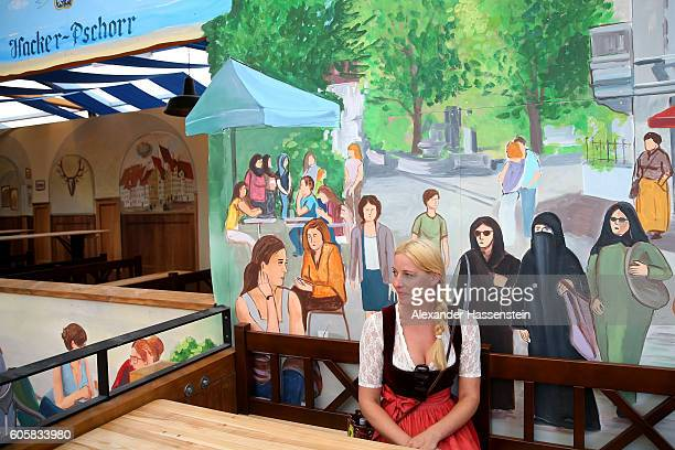 A woman sits under a painting inside the HockerPschorr tent that shows a woman in a burka and other Muslim women wearing headscarves in what tent...