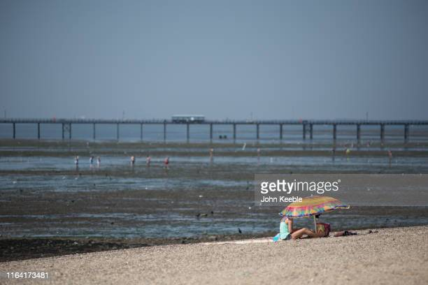 A woman sits under a parasol on the beach on July 25 2019 in SouthendonSea United Kingdom The Met Office issued a weather warning from 3pm this...
