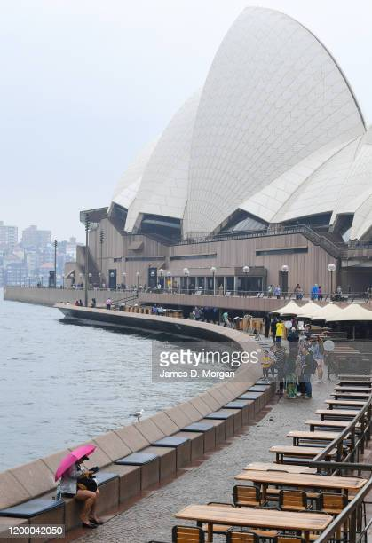 A woman sits underneath her umbrella beside the Opera House on January 17 2020 in Sydney Australia A severe thunderstorm warning has been issued for...
