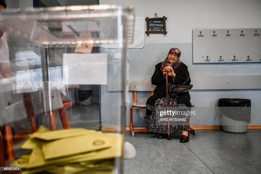 A woman sits waiting to cast her vote in snap twin Turkish presidential and parliamentary elections in Istanbul on June 24, 2018. - Turks began voting in dual parliamentary and presidential polls seen as the President's toughest election test, with the opposition revitalised and his popularity at risk from growing economic troubles.