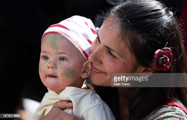 A woman sits with a baby as they watch a Beltane May Day celebration in Glastonbury main street on May 1 2013 in Glastonbury England Although more...
