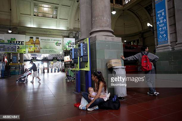 A woman sits with a baby in the nearly deserted Retiro Train Station in Buenos Aires Argentina on Thursday April 10 2014 Argentina's biggest unions...