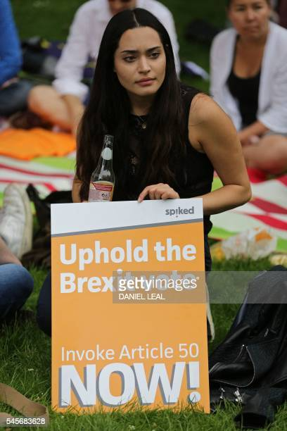 A woman sits with a proBrexit placard as a group of people set up a counter demonstration to a group taking part in a picnic against Brexit organised...