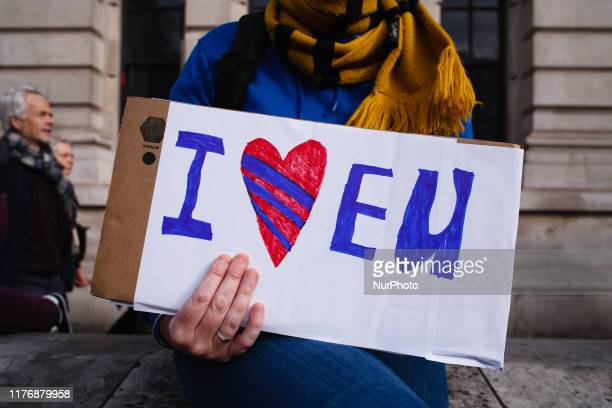 A woman sits with an 'I love EU' placard on Whitehall during the mass 'Together for the Final Say' march organised by the 'People's Vote' campaign...